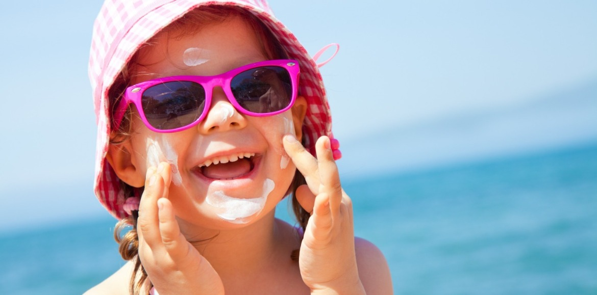 little girl wearing hat, sunglasses, and sunscreen on the beach | Ward Realty