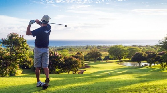 man playing golf near the beach | Ward Realty