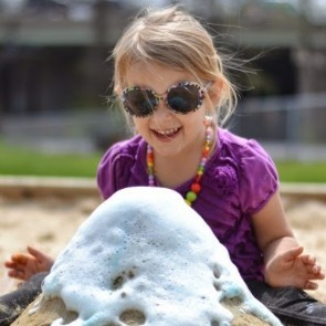 child with sand volcanoes | Ward Realty Topsail Island