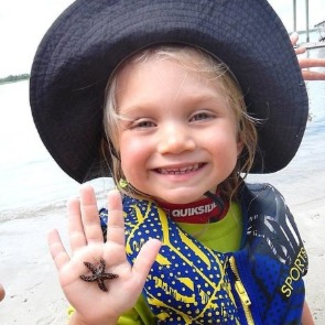 child holding a starfish | Ward Realty Topsail Island